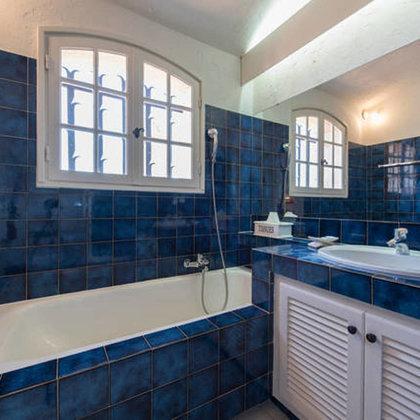 Salle de bain avec baignoire, douche et vue de mer